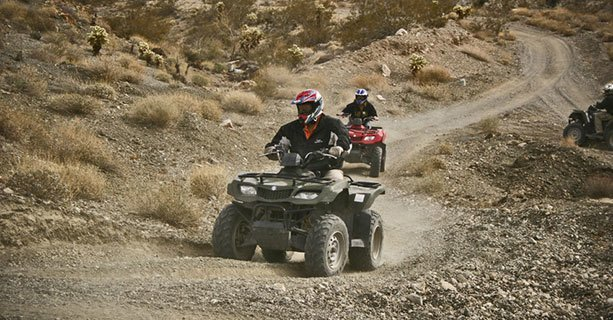 Sightseers driving ATVs through the desert.
