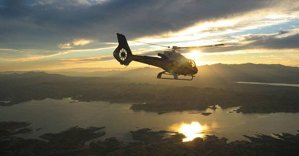 A helicopter flies over Lake Mead as the sun sets in the background.