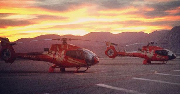 Two helicopters parked on a tarmac with the sun setting behind them.
