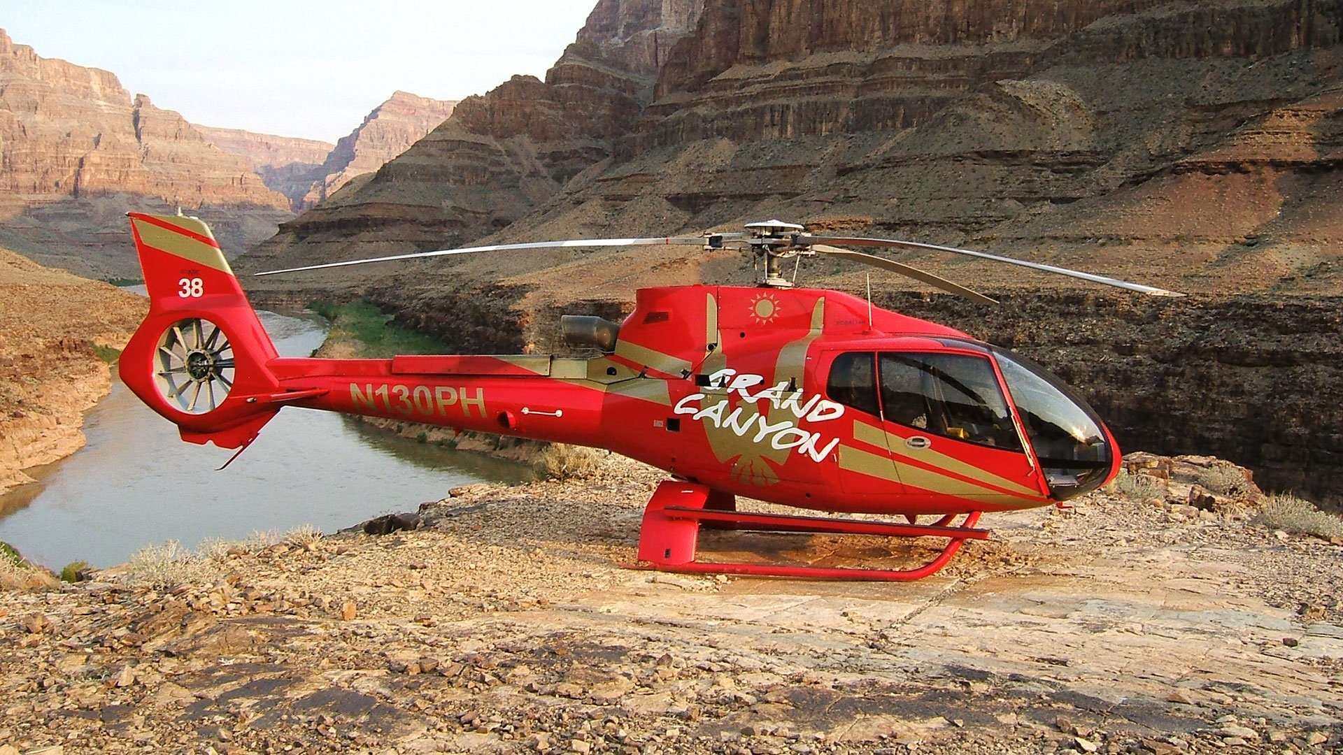 An EC-130 helicopter landed at the bottom of the Grand Canyon with the Colorado River in the background.