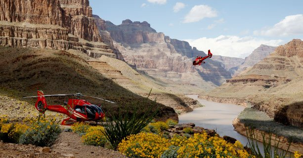 A helicopter landed at the bottom of the Grand Canyon and another taking off.