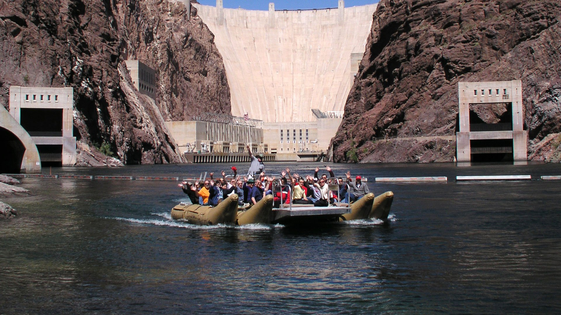 Passengers on a river raft with the Hoover Dam in the background.
