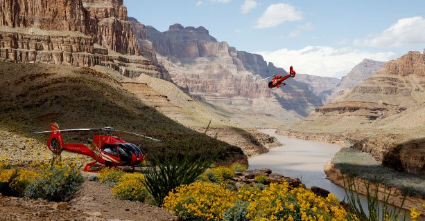 Two helicopters descending to the floor of the Grand Canyon West.