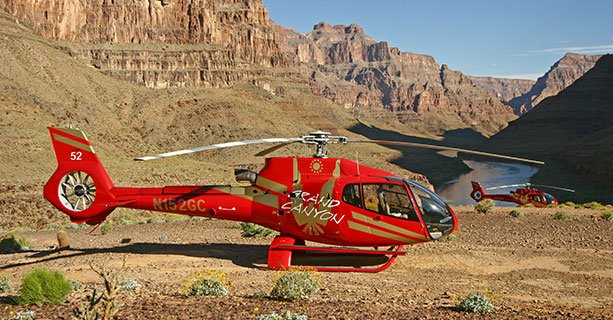 A helicopter landed at the bottom of the Grand Canyon with the Colorado River behind it.
