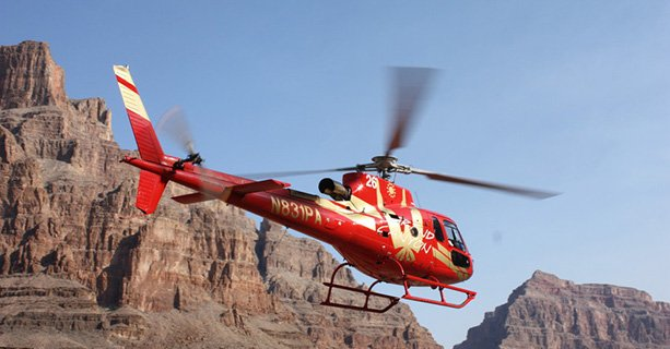 A helicopter cruises between the walls of the Grand Canyon West.