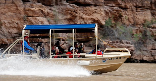 A pontoon boat filled with passengers sails down the Colorado River.