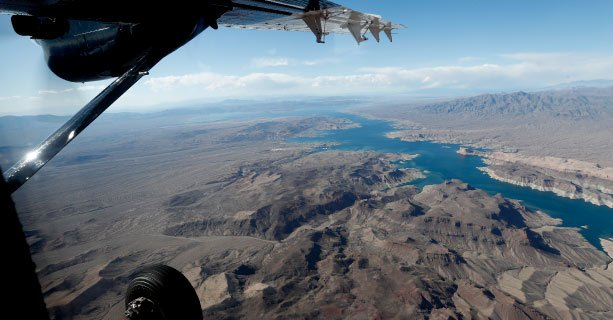 A view of Lake Mead and the surrounding desert from an airplane window.