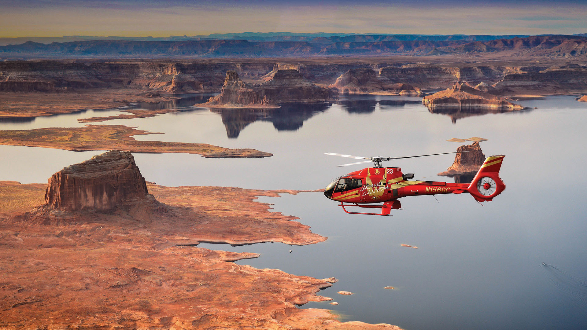 A red helicopter flies over a lake surrounded by desert.