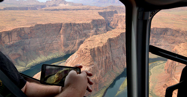 A passenger photographs a desert scene on their phone.