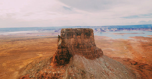 Tower Butte stands in front of a scenic desert landscape.