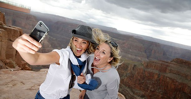 Two women pose for a picture at the edge of the Grand Canyon West.