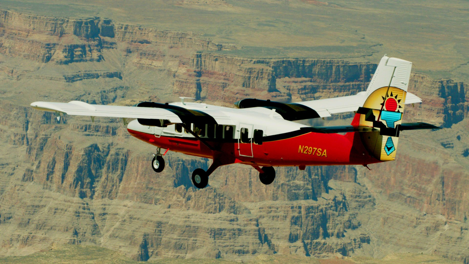 A Twin Otter plane flying over the Grand Canyon West Rim.