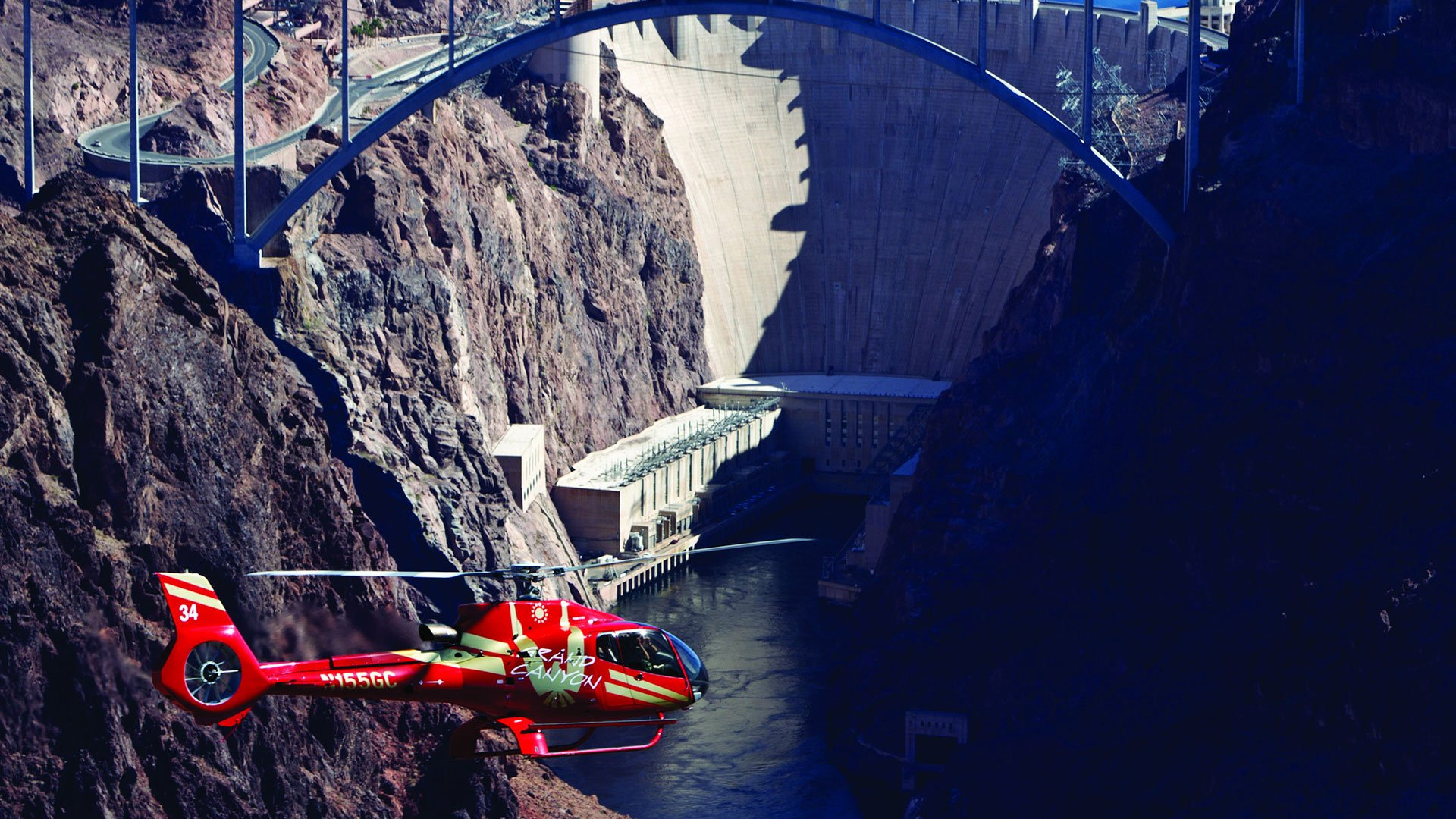 A red helicopter soars in front of Hoover Dam.