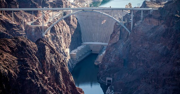 The Hoover Dam with a large bridge in the foreground.