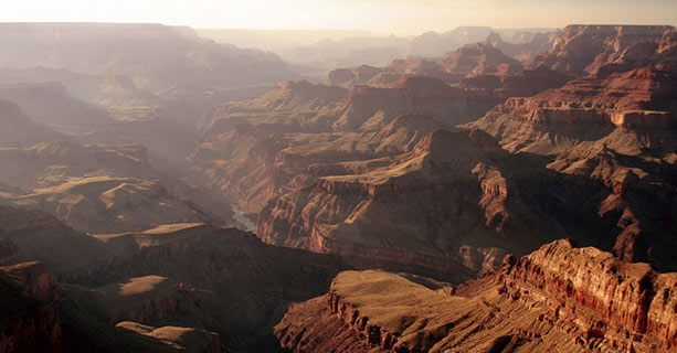 The misty expanse of the Grand Canyon, cut by the Colorado River.