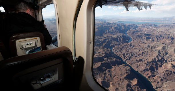 An aerial view of the Colorado River seen from the window of a Grand Canyon airplane tour.