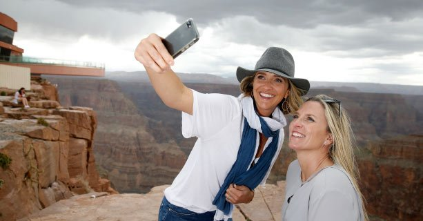 Two women pose for a photo at the canyon's edge with the Skywalk behind them.'