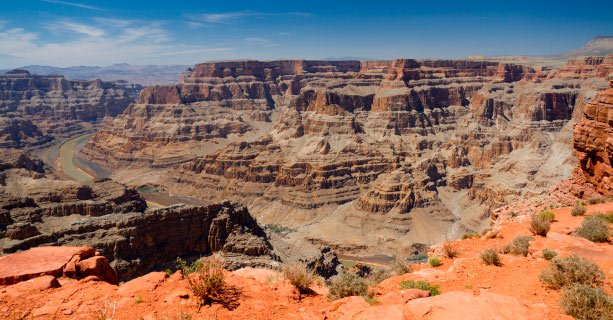 A scenic panorama of the Grand Canyon West with the Colorado River below.