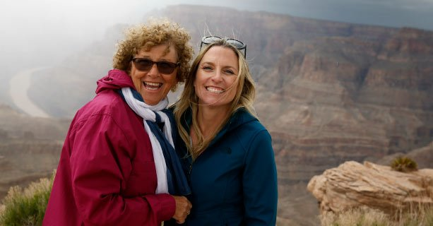 Two women pose smiling at the edge of the Grand Canyon West.