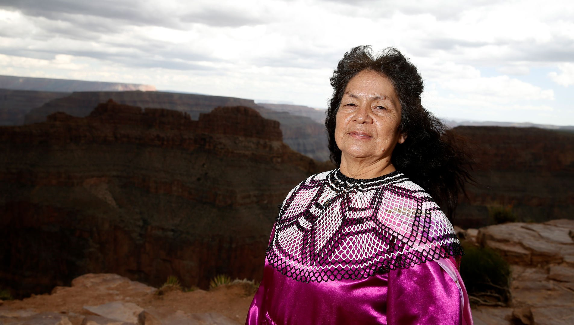 A Hualapai woman wearing traditional garb with the Grand Canyon in the background.