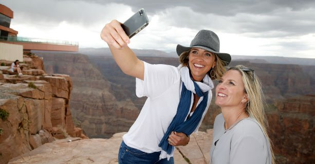Two women pose for a photo with the Grand Canyon and Skywalk Bridge behind them.'