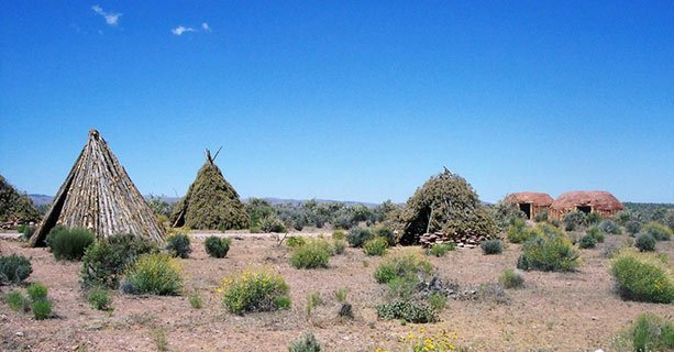Several traditional Native American dwellings surrounded by a desert landscape.