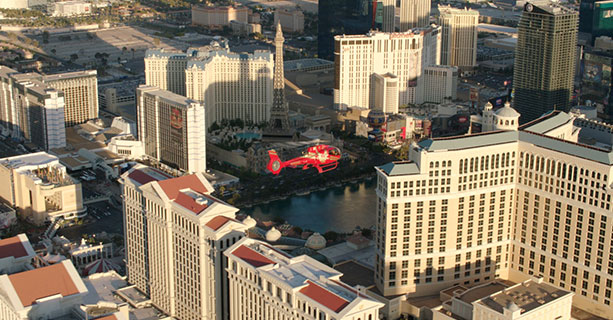 A red helicopter flies over the Las Vegas Strip.