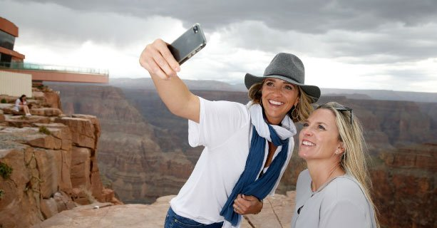 Two women pose for a photo at the Grand Canyon with the Skywalk in the background.