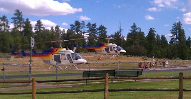 Two Bell helicopters taking off from the Grand Canyon National Park heliport