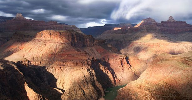The Grand Canyon lit by partly cloudy skies.
