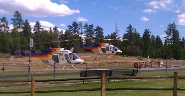 Two Bell helicopters landing at the Grand Canyon National Park heliport.