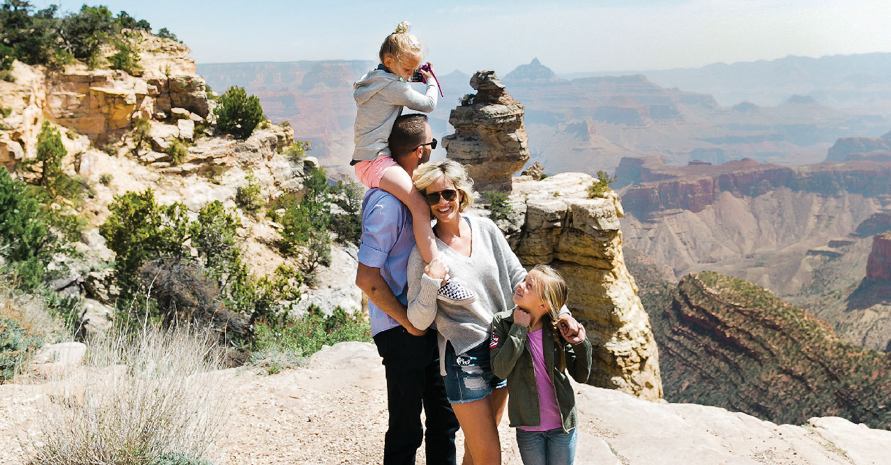 A family enjoying a moment together at the edge of the Grand Canyon.