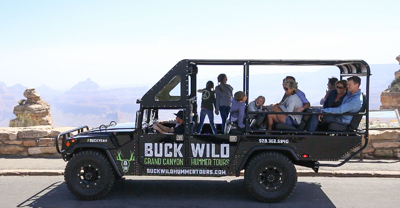 A family enjoying Grand Canyon sightseeing aboard an open-air Hummer.