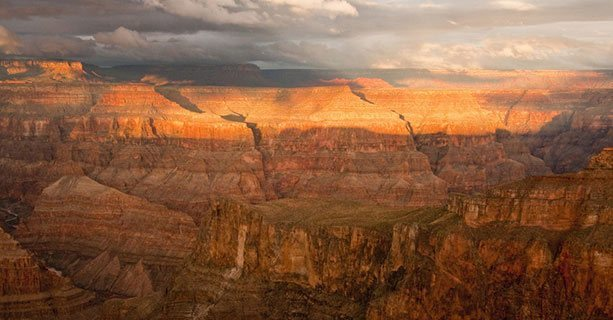 The sun sets across a Grand Canyon landscape.'