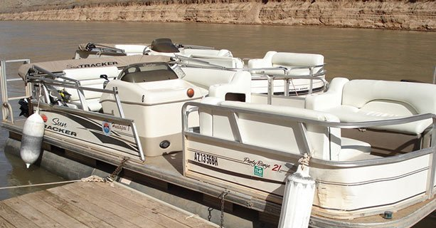A touring pontoon boat docked along the Colorado River.'