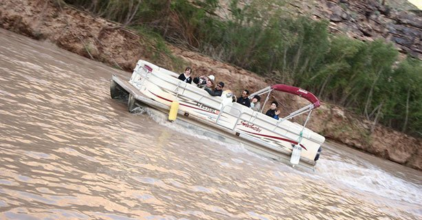 Sightseers travel down the Colorado River on a pontoon boat.