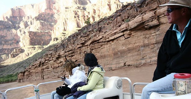 Two women watch the canyon walls pass by on a pontoon boat travelling down the Colorado River.