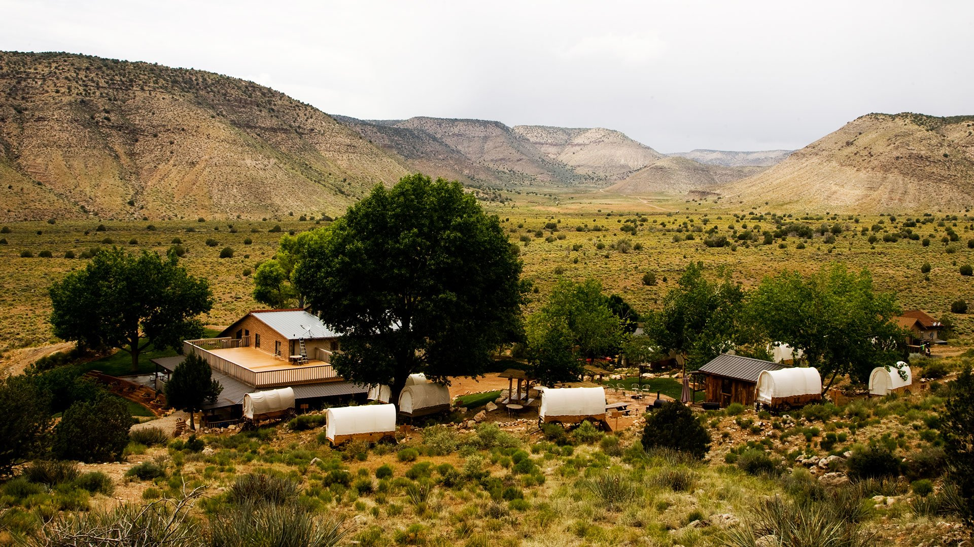 A view of Bar 10 Ranch, their covered wagons, and trees