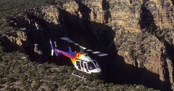 Bell helicopter flies over the Grand Canyon.