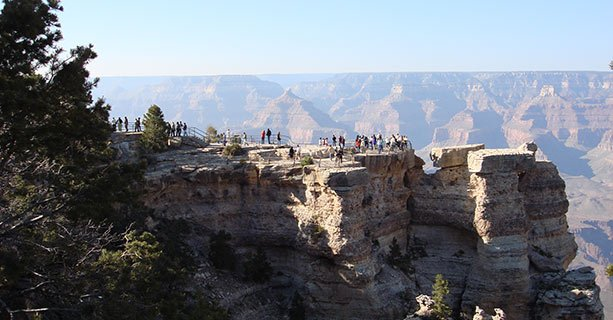Visitors stand on a rocky overlook at the Grand Canyon National Park.