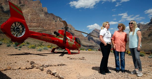 Two female passengers and a female pilot talk in front of a helicopter on the Grand Canyon floor.