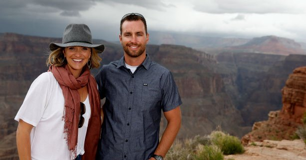 A couple poses together at the edge of the Grand Canyon West.