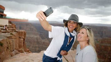 Two women take a photo together at the canyon's edge with the Skywalk Bridge behind them.