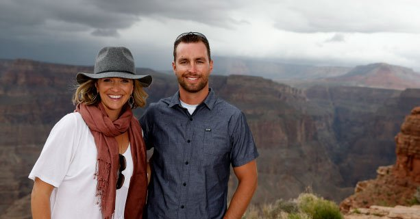 A couple poses together in front of the Grand Canyon.'