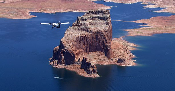 An airplane tour flies across the blue waters of Lake Powell.