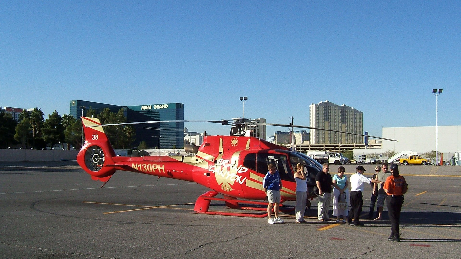 Passengers preparing to board their helicopter tour with the Las Vegas Strip in the background.