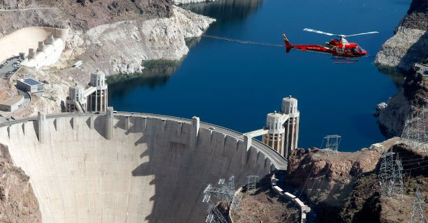 A helicopter soars over the Hoover Dam and Colorado River.