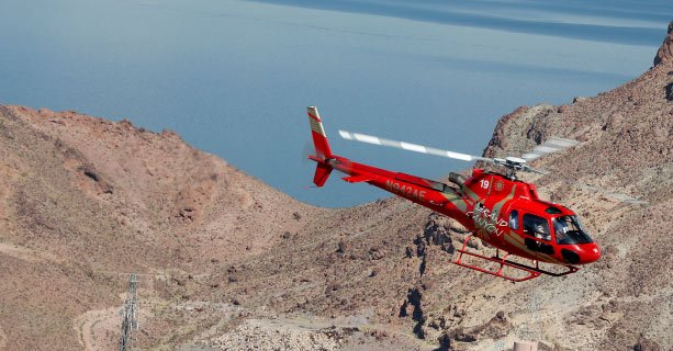 Bell helicopter soaring over the desert landscape and Lake Mead.