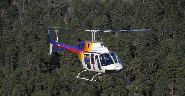 A Bell helicopter hovering over the Kaibab National Forest.