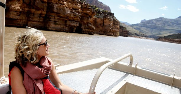A woman sightseeing aboard a pontoon boat travelling down the Colorado River.